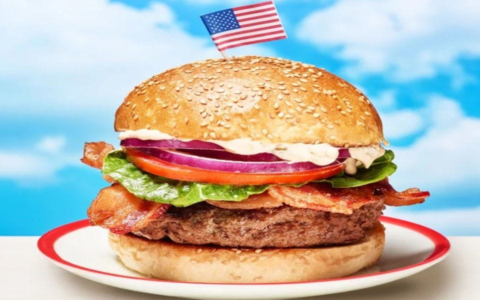 A stacked cheeseburger with an American Flag toothpick stuck in its bun.