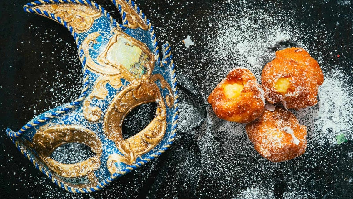 A Mardi Gras carnival mask on a dark background next to pastries covered in powdered sugar.