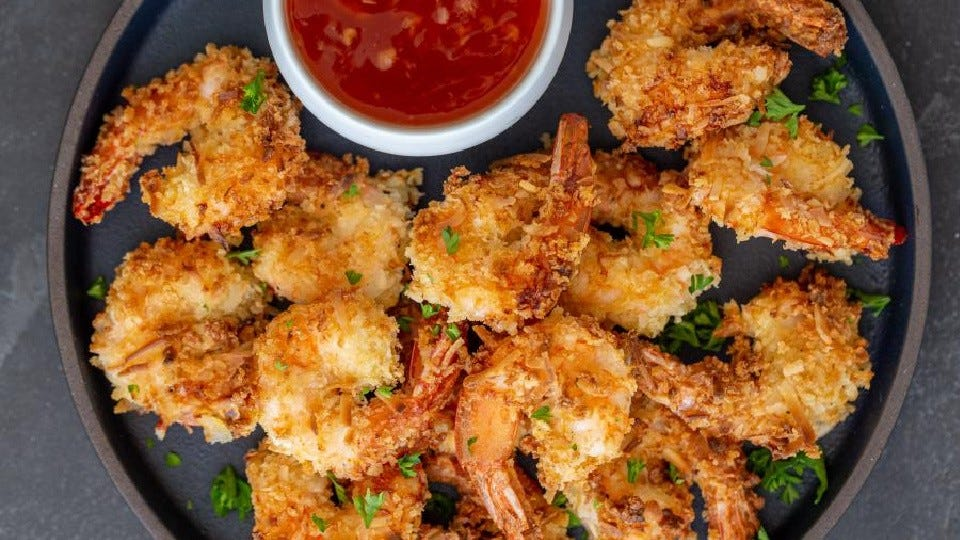 A round brown plate filled with a pile of hot air fried coconut shrimp, with a side of sweet chili dipping sauce.