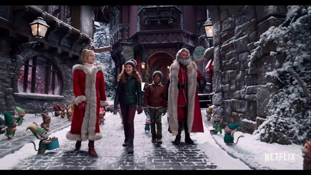 Santa, Ms. Claus, and two children walk down a snowy village path.
