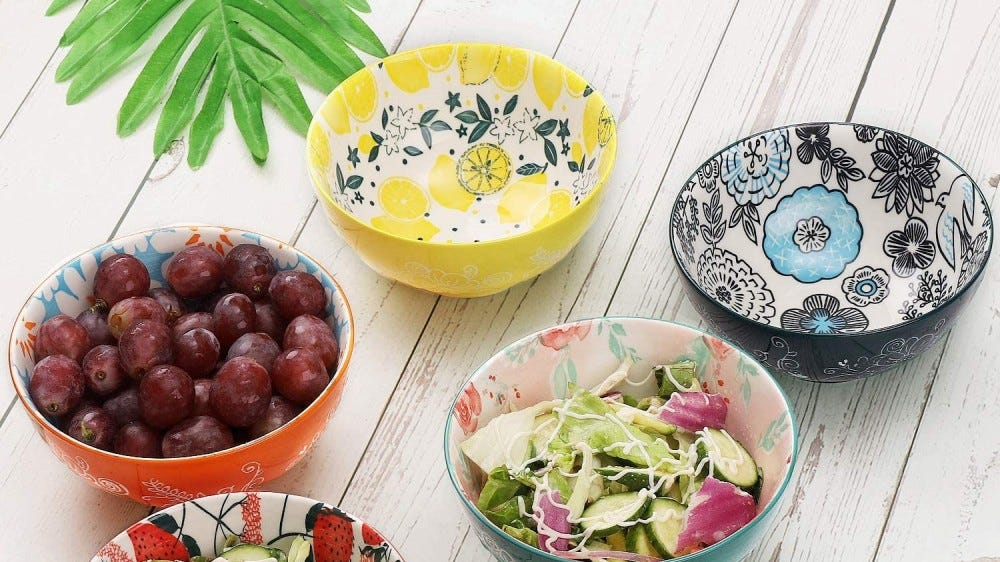 Colorful bowls on a table filled with fruits and salads.