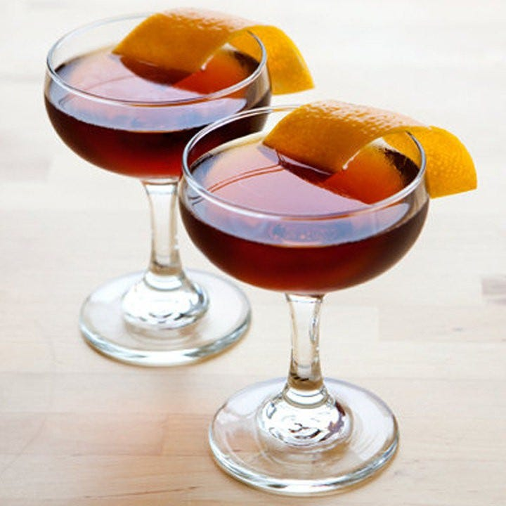 Two Hanky Panky cocktails with orange peels lying over the side.