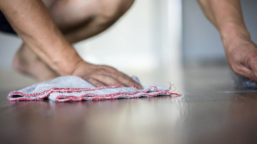 A person wiping a hardwood floor with a soft towel.