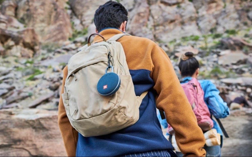 Man hiking with a waterproof speaker attached to his backpack.