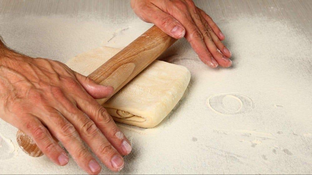 Hands rolling out croissant dough.