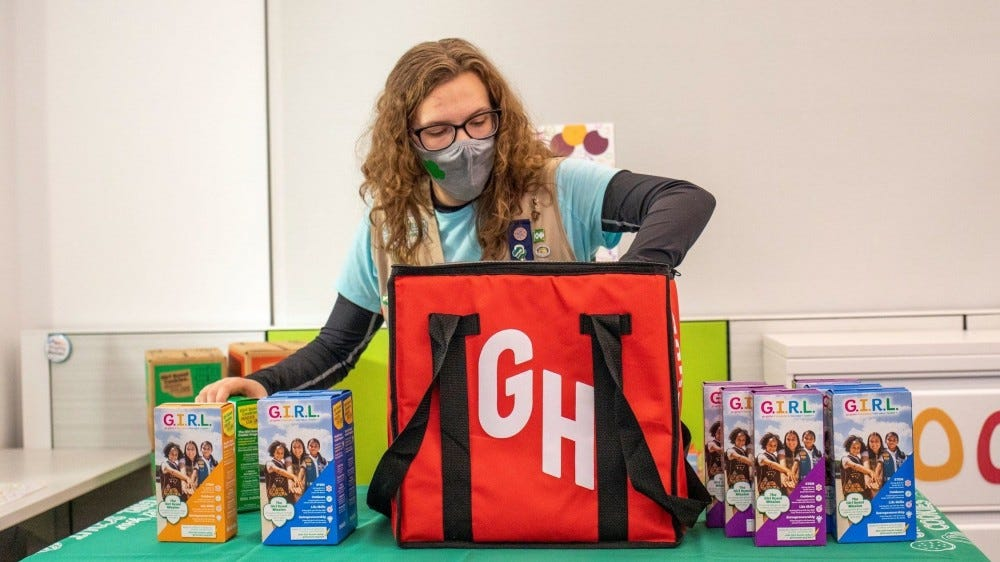 A young girl packing boxes of Girl Scout cookies in a GrubHub bag.
