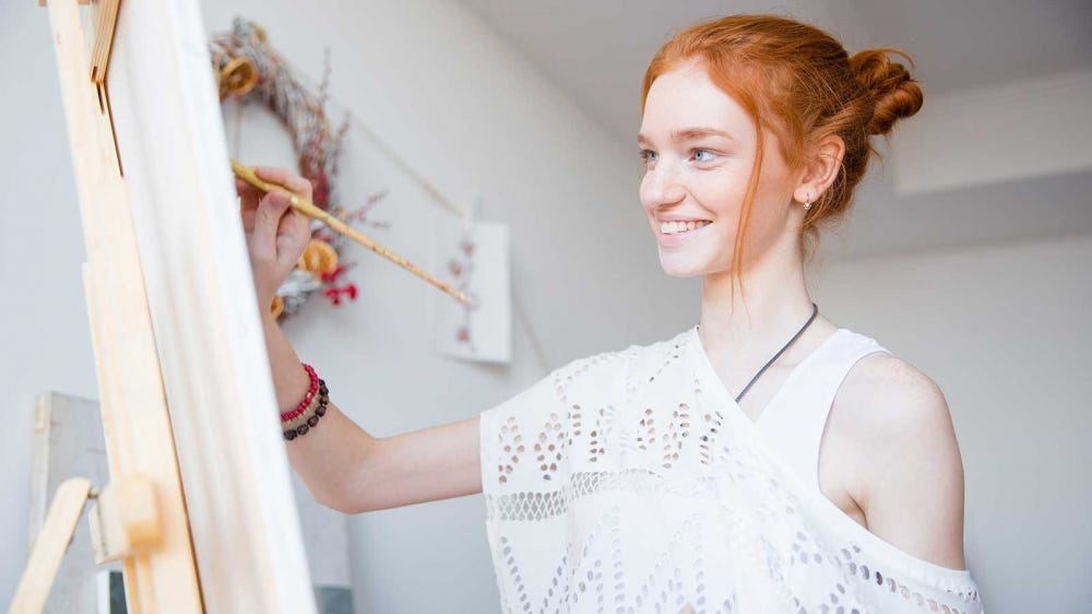 A teenage girl painting on an easel.