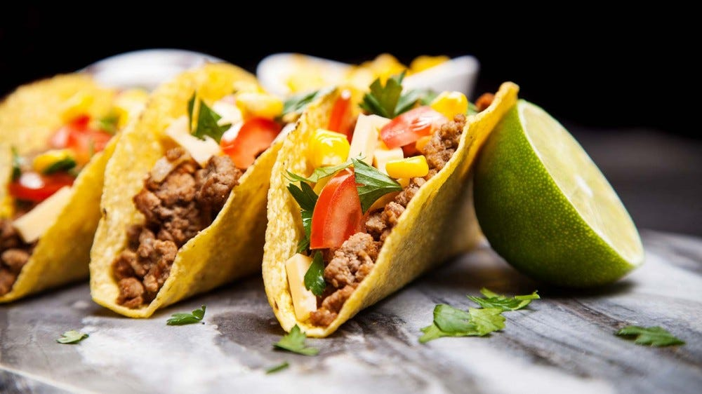 Three hard-shell tacos sitting next to half a sliced lime.