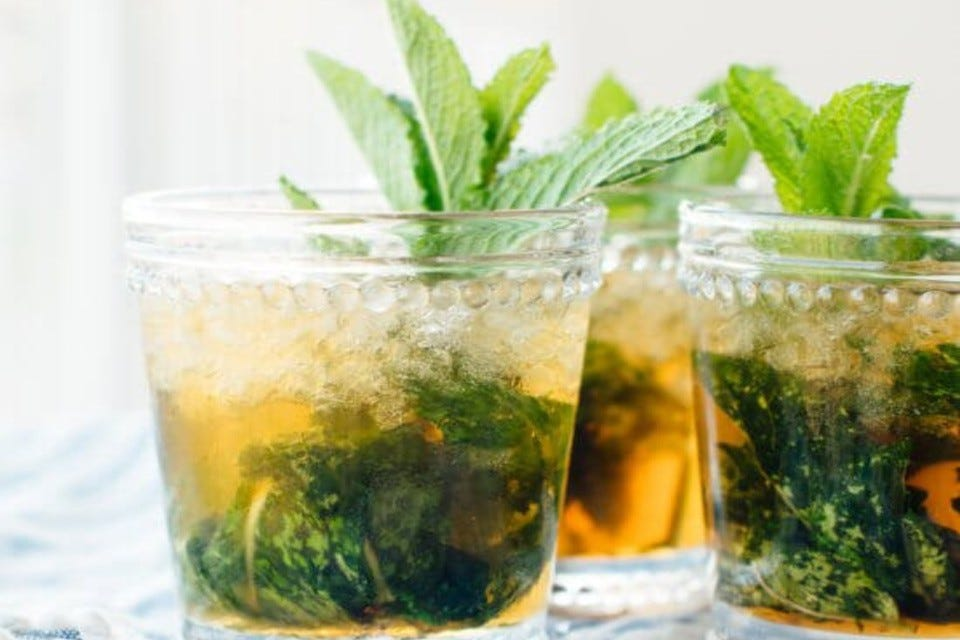 Three glasses filled with maple mint juleps, garnished with fresh mint leaves.