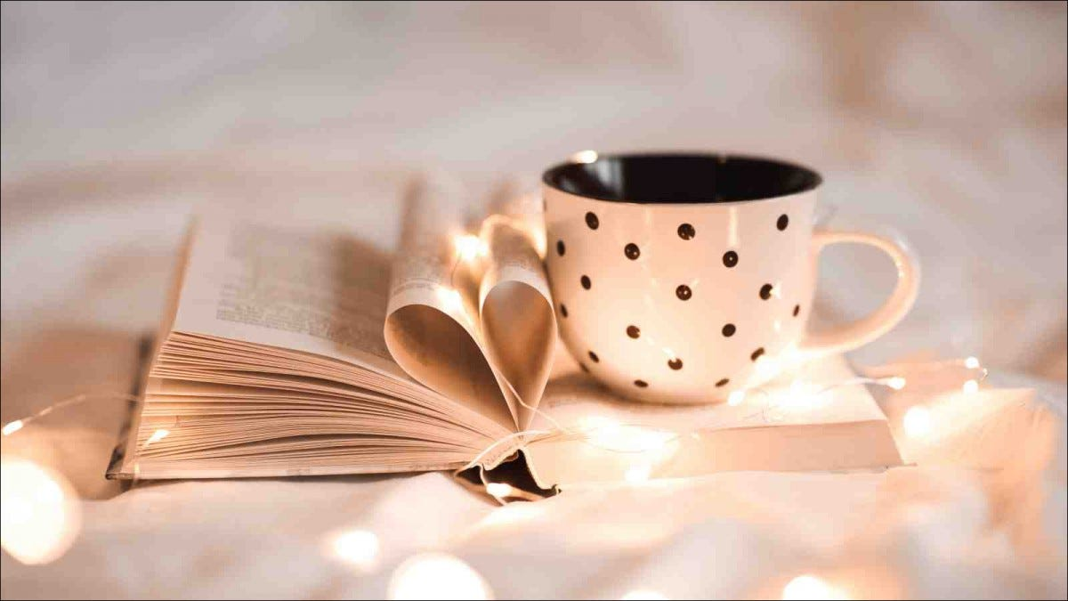 Open book with folded sheets in heart shape and cup of tea