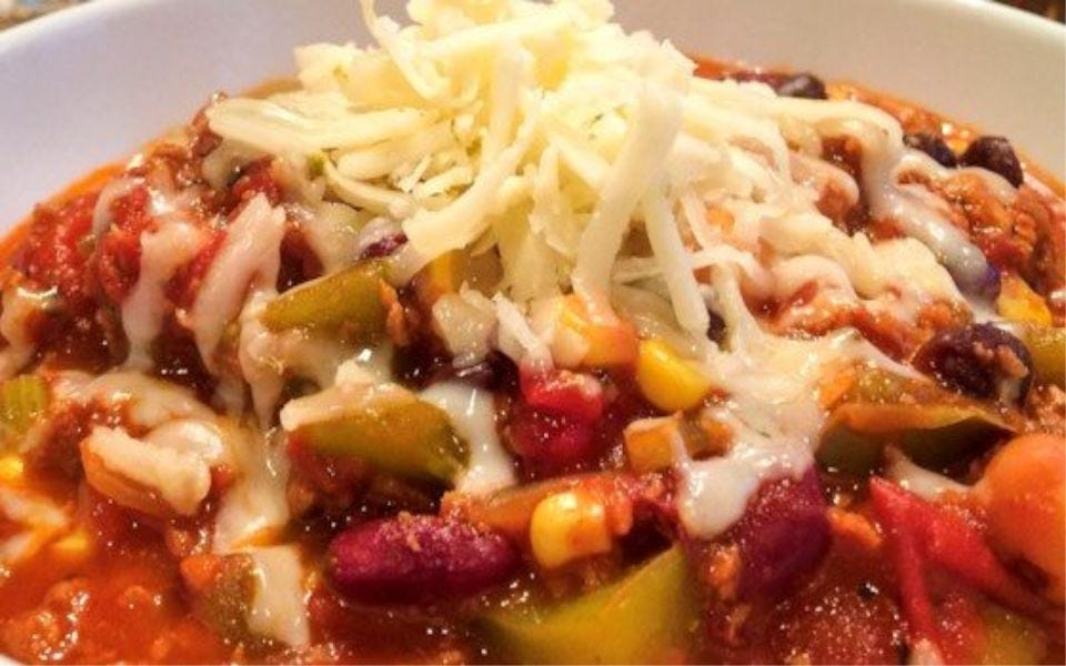 A bowl of vegetarian chili topped with shredded cheese