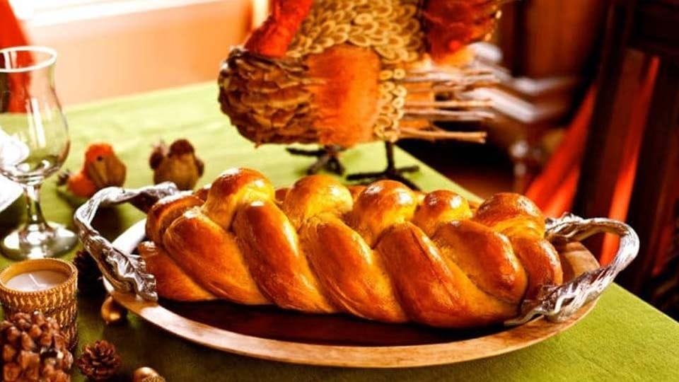A challah bread on a silver platter, surrounded by fall decorations like pine cones, a turkey statue, and candles.