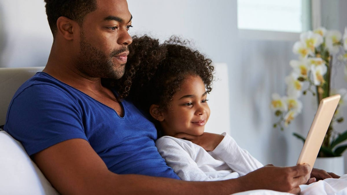 A man and little girl watching something on a tablet.