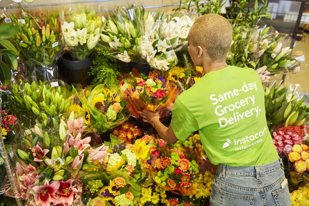 An Instacart shopper examines a display full of floral bouquets.
