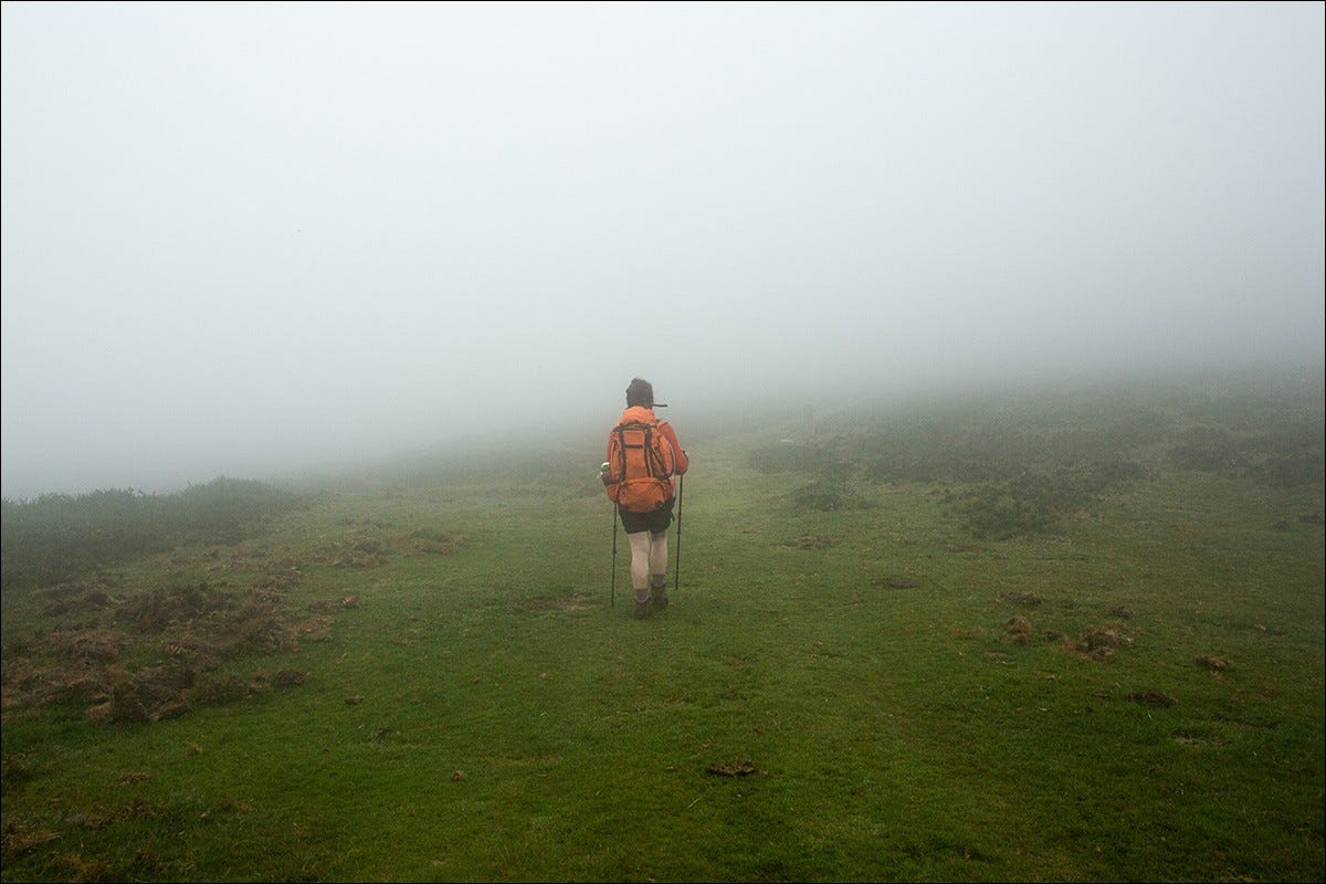 A backpacker walking on a misty hilltop.