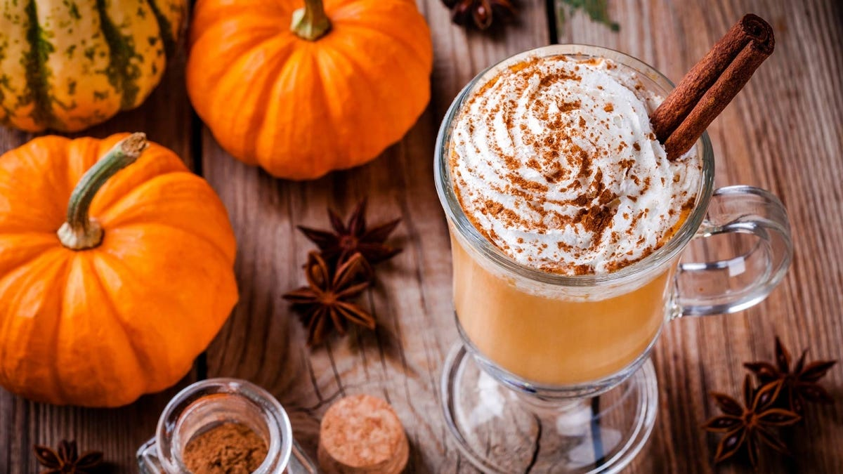 A pumpkin-spice latte sitting on a wooden table surrounded by fall decorations and seasonings.