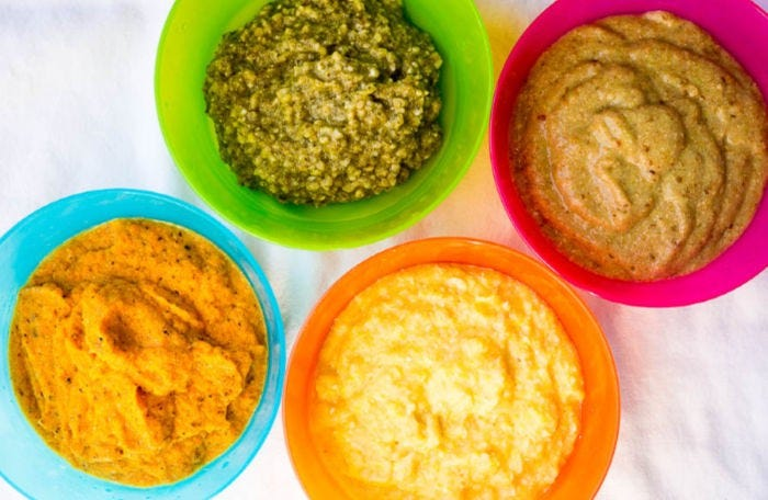 Four colorful bowls with four different baby food purees made from a pressure cooker