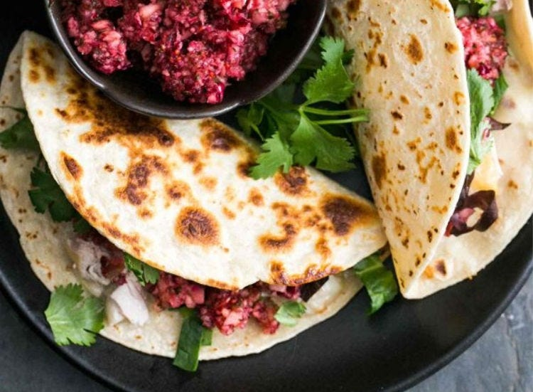 Two Corn tacos filled with turkey, lettuce, cilantro and a side of cranberry salsa.