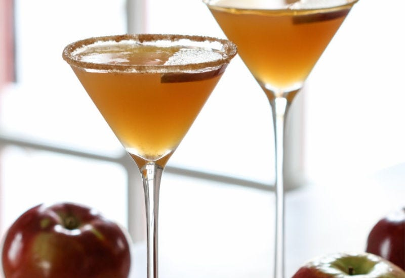 Two Caramel Apple Martinis surrounded by apples.
