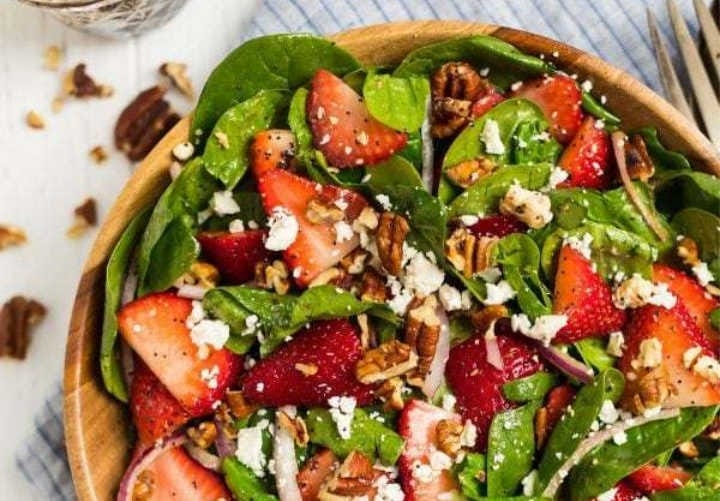 A freshly tossed spinach salad, topped with sliced strawberries, pecans, red onion and crumbled cheese.