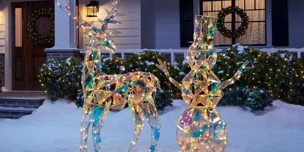 An iridescent reindeer and snowman sit lit up in front of a snow-covered home.