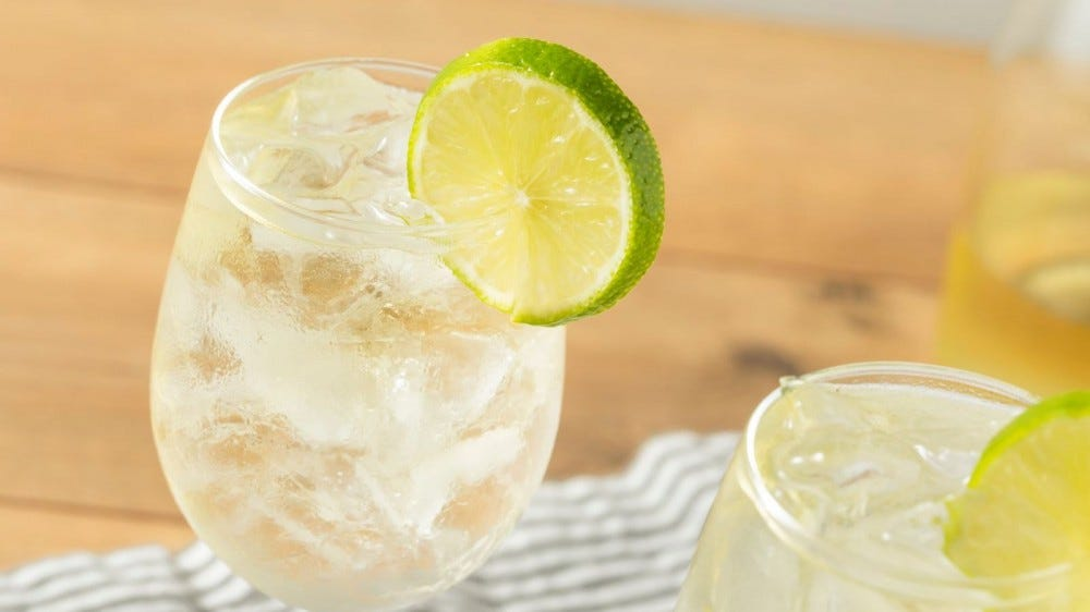 Two white wine spritzers with limes.