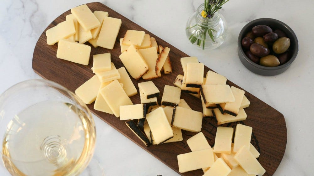 A cutting board covered in gourmet cheese.