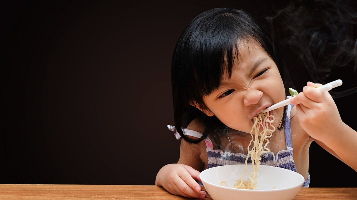 Young girl eating a bowl of steaming hot noodles with chopsticks.