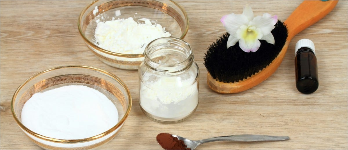 Homemade dry shampoo in a jar made of powder corn starch, baking soda and essential oil