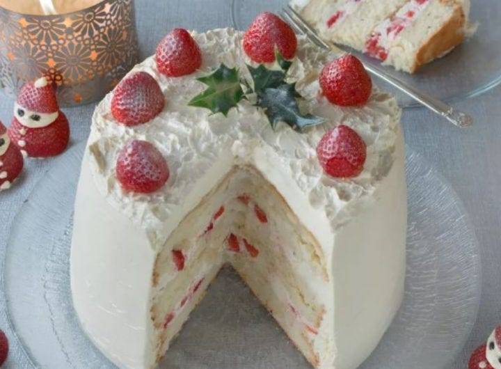A beautifully decorated Christmas cake topped with fresh strawberries.