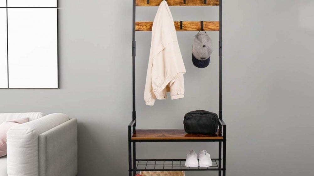 The HOMEKOKO Coat Rack with a jacket and ball cap hanging on it, a bag sitting on the top shelf, and pair of shoes on the bottom rack.