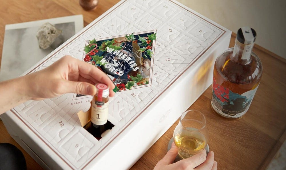 A man opening a whiskey calendar to sample a new whisky every day.