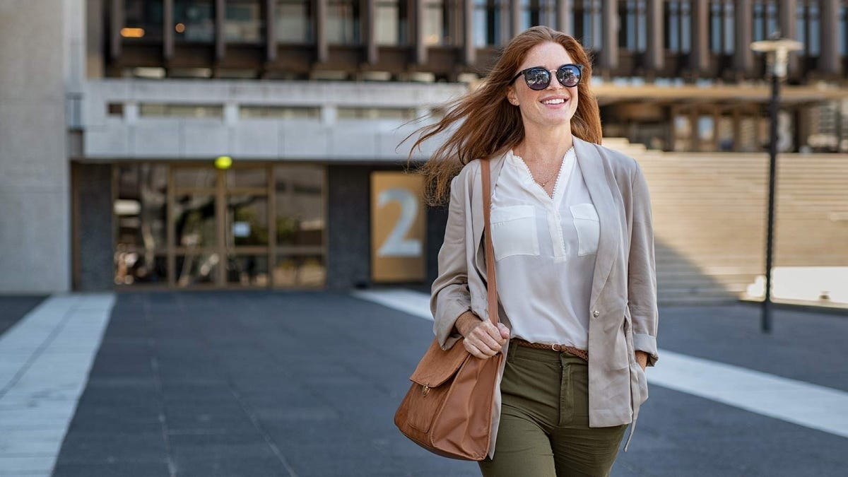 A smiling woman walking out of a building.