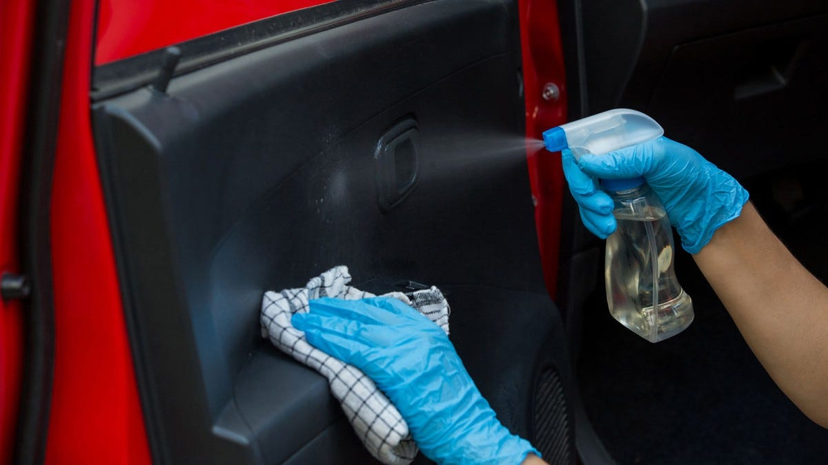 Person disinfecting a car with cleaning spray and a rag.
