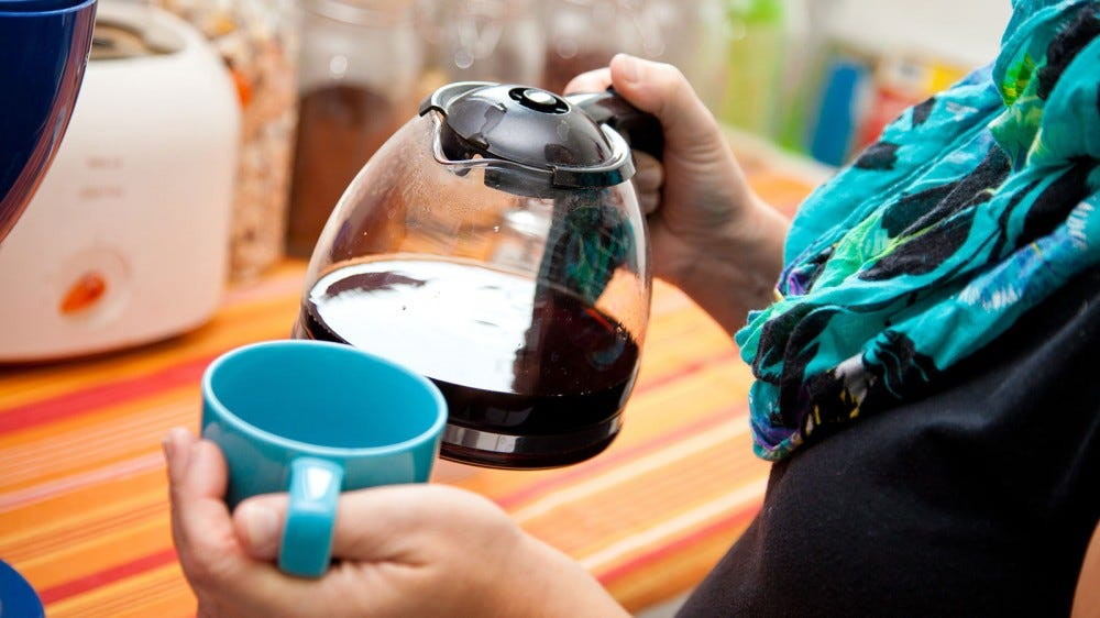A woman holding a mug and a traditional drip coffee carafe.