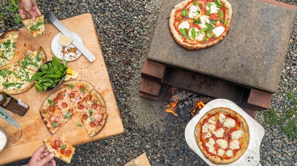 A DIY brick pizza oven beside a cutting board with pizza on it.