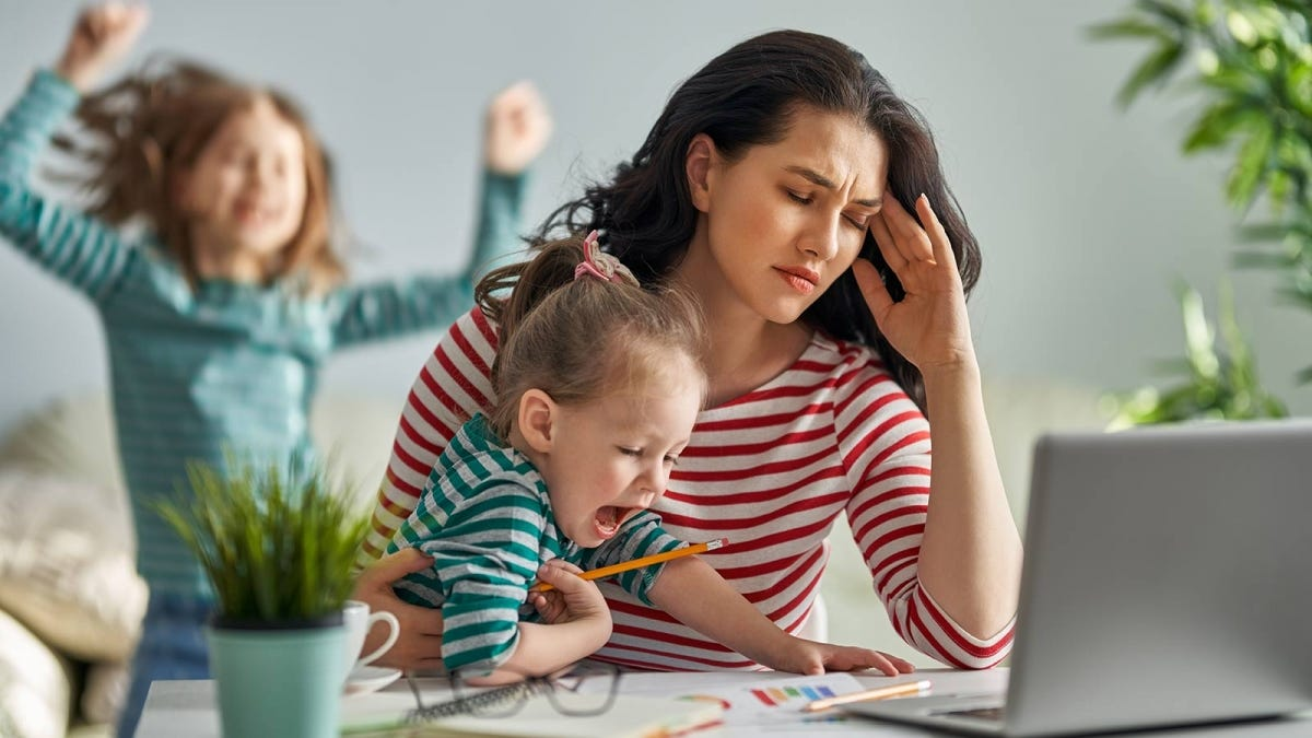 Woman stressed, working at home with her children yelling around her.
