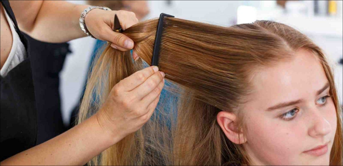 closeup of hairdresser styling teen girl's hair