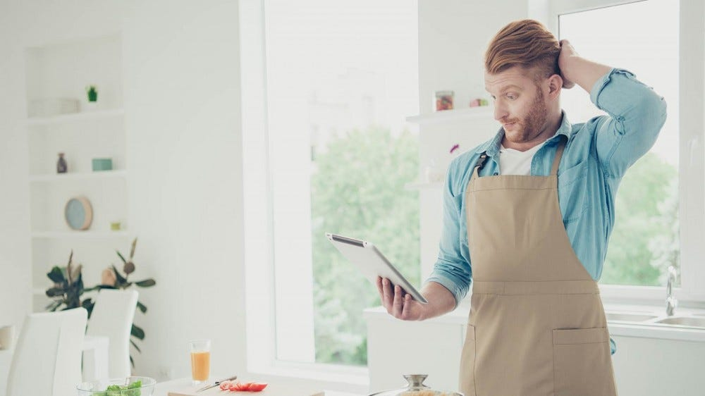 A man looking at a recipe on his iPad, confused by some of the cooking terms.