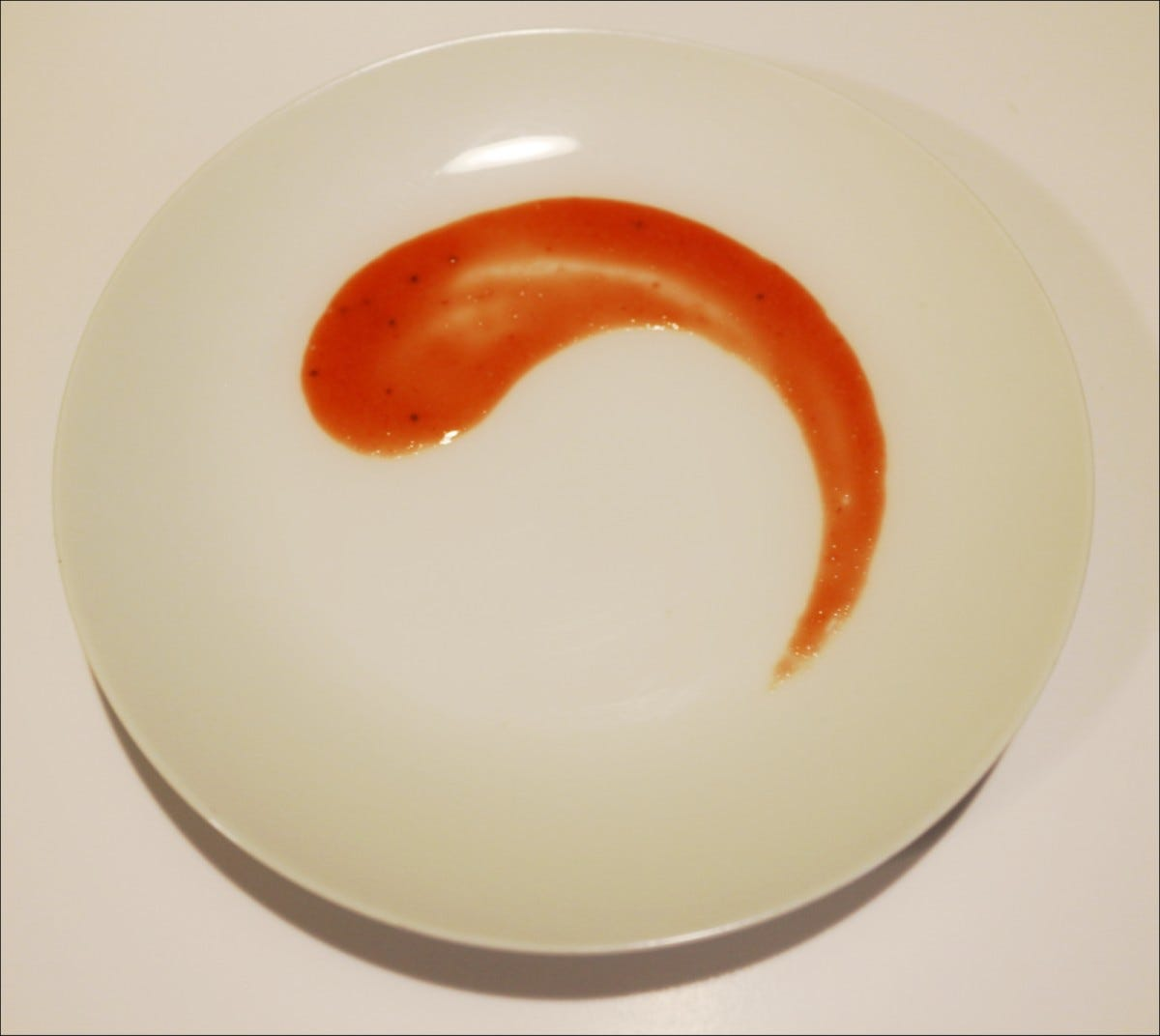 Strawberry puree design created by dragging the bottom of a spoon following the shape of a round, white plate.