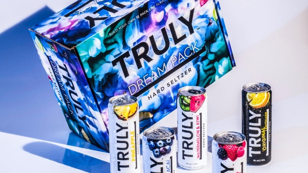 A tie dye box of Truly seltzers is tilted on its side with cans of Truly around it.
