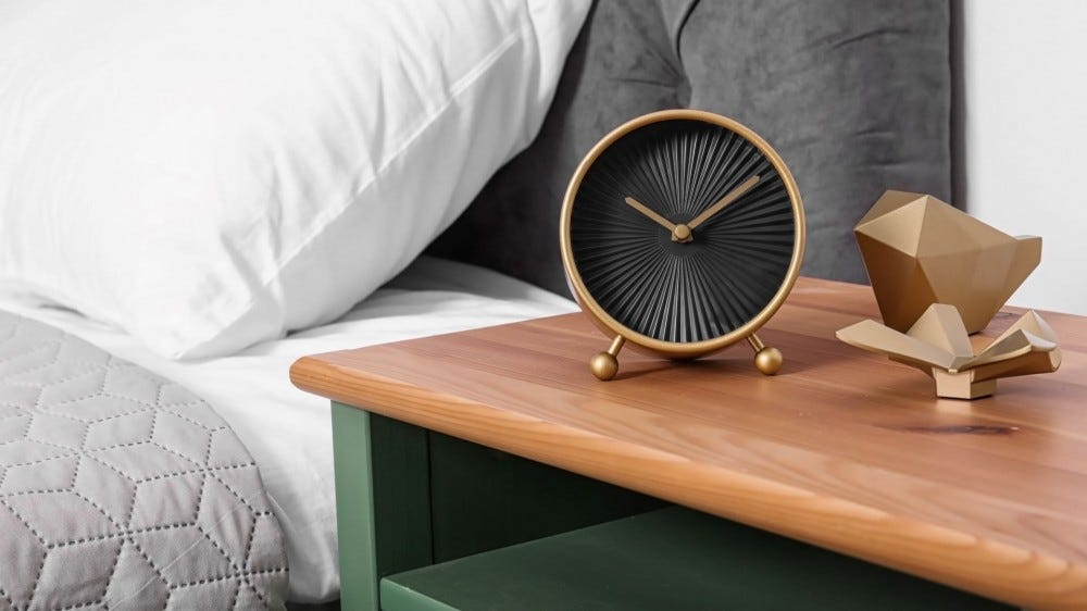 A nightstand with a clock and two metal sculptures on it.