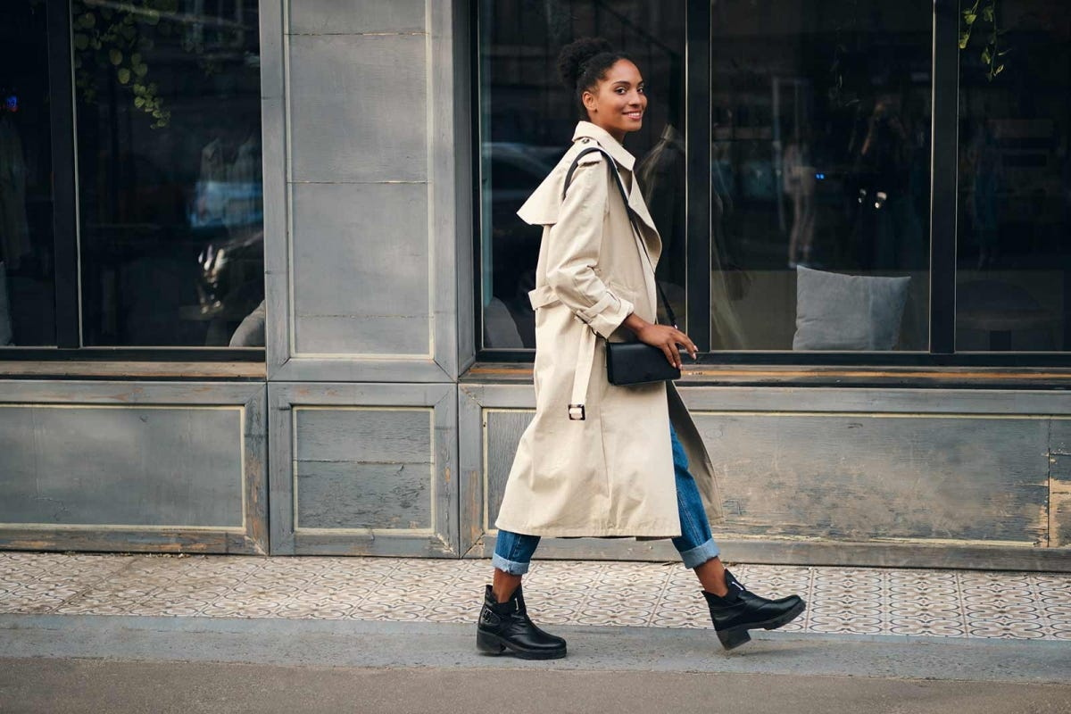 Woman walking down the street wearing a light-colored trench coat.