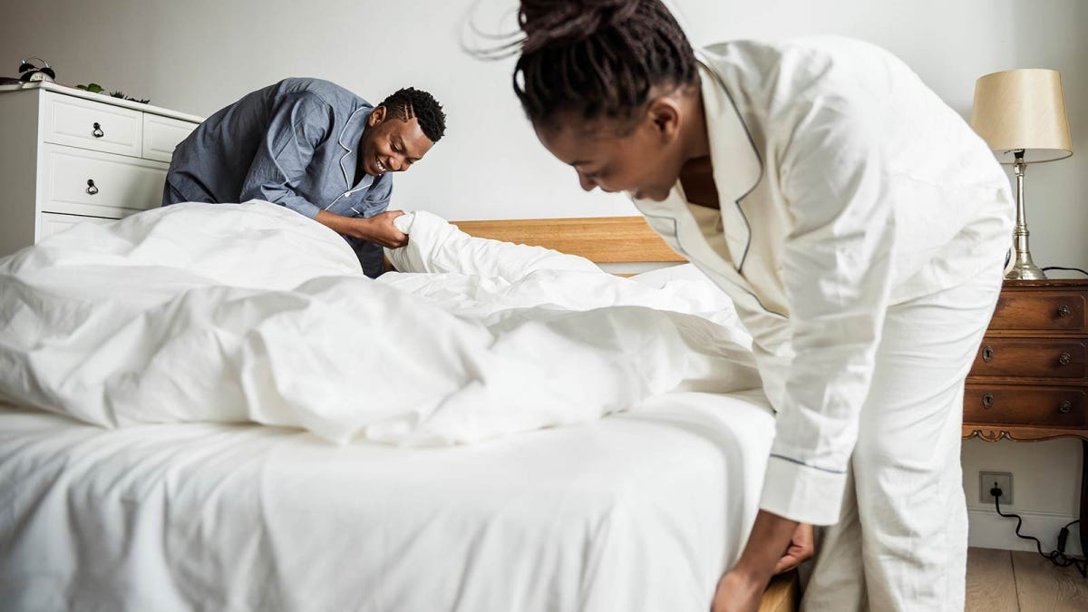 couple wearing pajamas making a bed with white linens
