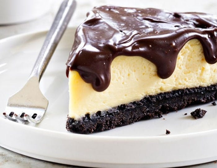 A slice of baileys cheesecake with a ganache on top and a fork on the side.