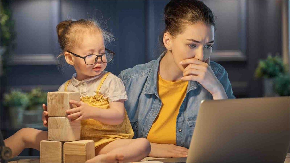 Young mother with toddler child working on the computer from home at night
