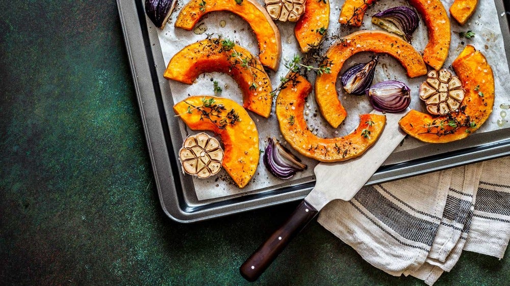 A baking tray of roasted squash on an emerald green countertop.