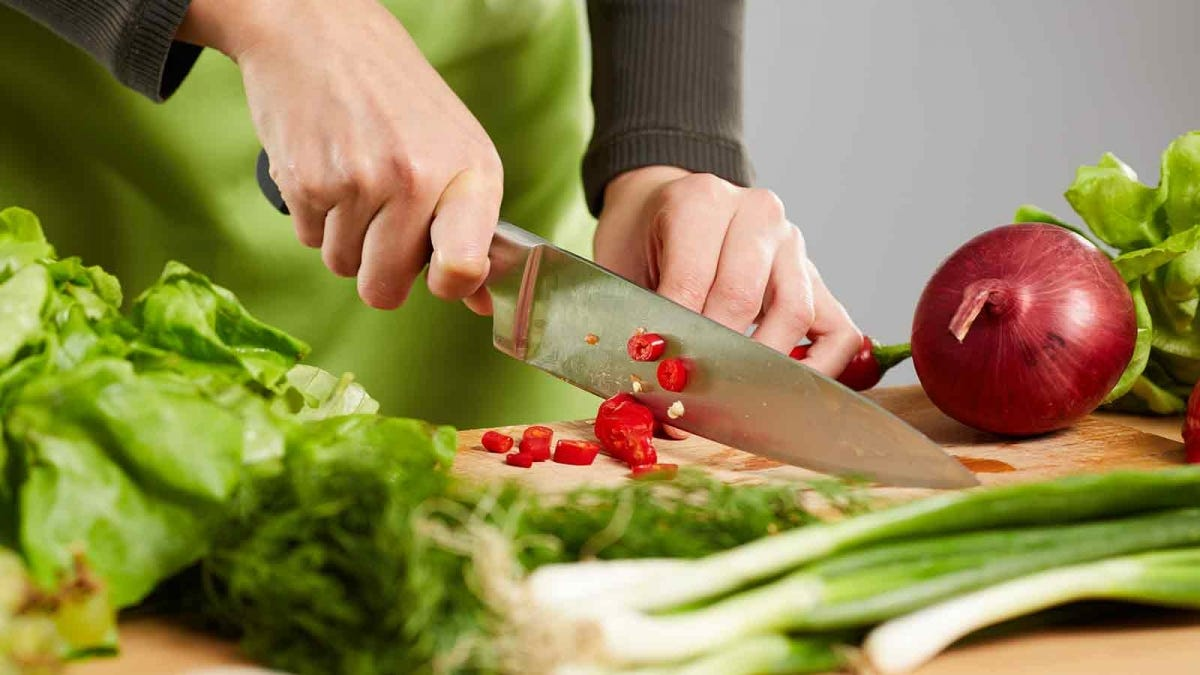 A woman's hands slicing vegetables with a chef knife.