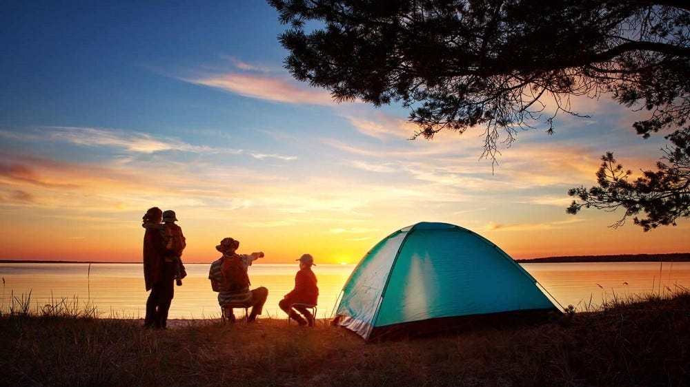 A family sitting on the edge of a lake outside their tent at sunset.