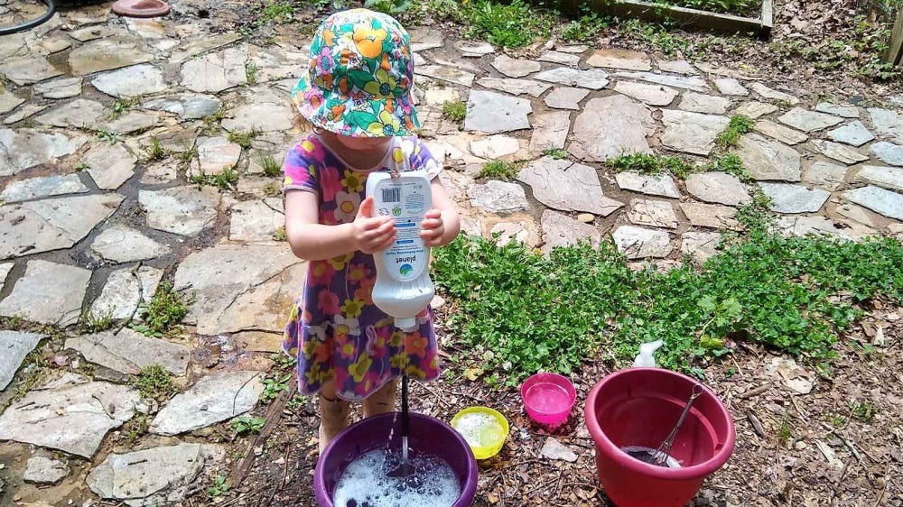 Toddler girl pouring dish soap into a purple bucket with bowls and a soup ladle on the ground.
